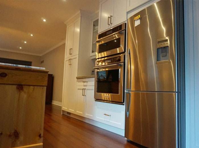Custom maple cabinets line the opposite wall and frames stainless steel microwave, oven and fridge.
