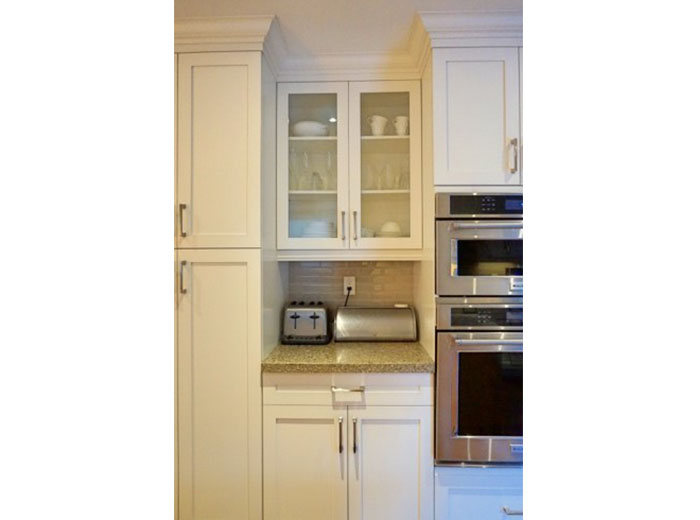 Glass cabinet doors and customized nook for small appliances.