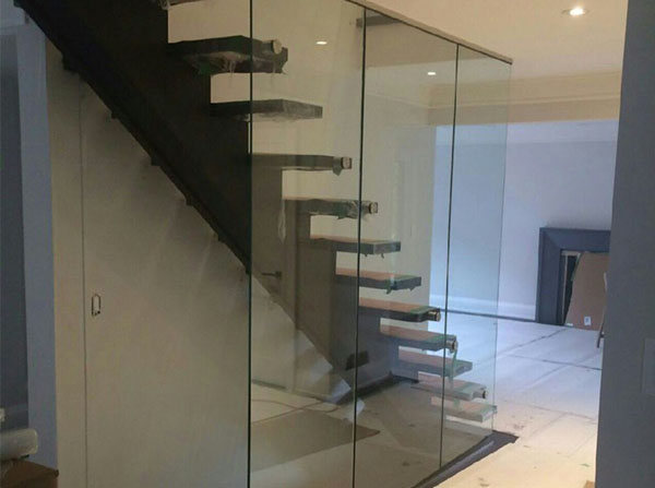 Modern staircase design with custom glass panels encasing stairwell