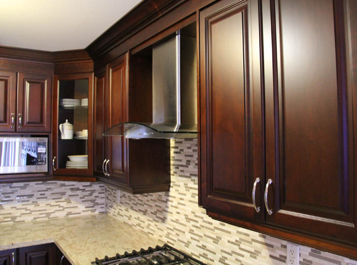 Custom kitchen cabinets with raised panel doors stained to dark cherry colour