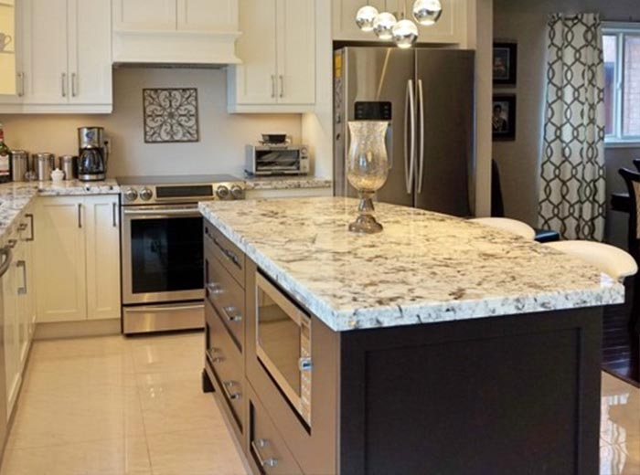 Alaska White Granite Countertop compliments the white maple cabinets and mocha stained island